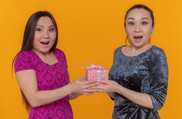 オレンジ色の壁の上に広く立って笑顔のプレゼントを開催する国際女性の日を祝う2人の幸せで驚きのアジアの女性