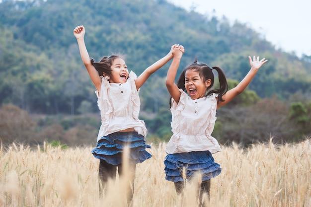 麦畑で一緒に遊んでジャンプを楽しんで2人の幸せなアジアの子女の子