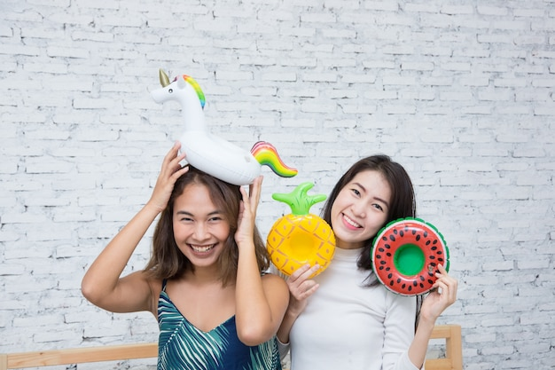Two happy asian girl playing with donut float