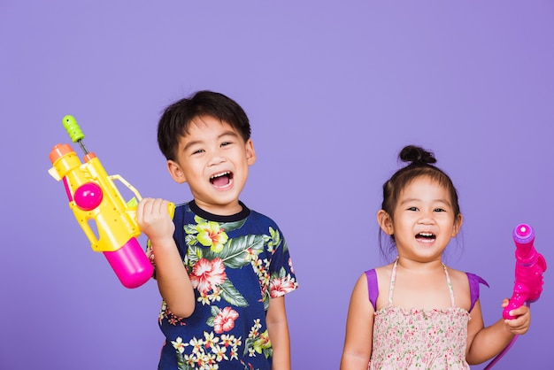 Two happy asian little boy and girl holding plastic water gun, thai children funny hold toy water pistol and smile,