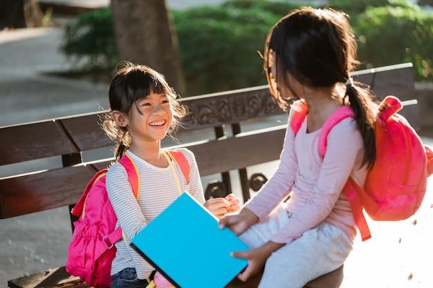 두 명의 행복한 아시아 학생 친구가 공원에서 공부하는 것을 즐깁니다.