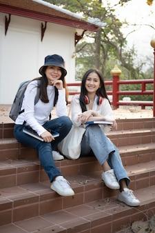 Два счастливых азиатских студента сидят на лестнице в университетском городке и улыбаются в камеру.