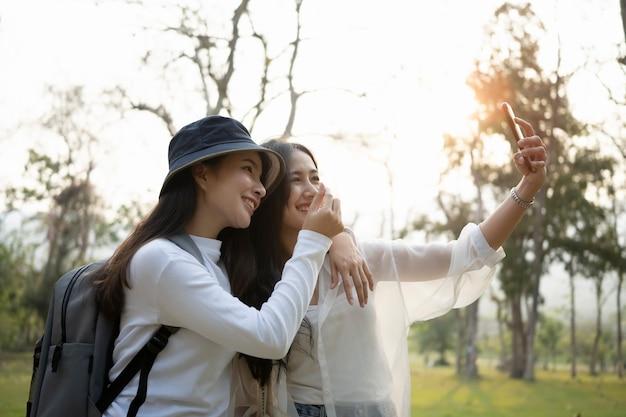 스마트 폰을 사용하는 행복한 아시아 학생 두 명이 대학 캠퍼스에서 쉬는 시간에 셀카를 찍습니다.