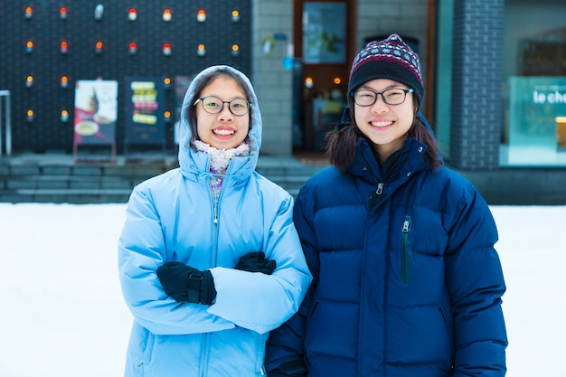 Two happy asian tourist teenagers standing in snow on a cold winter day at otaru, hokkaido, japan