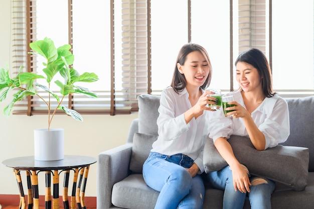 2人の幸せなアジアの女性の友人は、リビングルームで一緒に青汁を飲むのを楽しんでいます