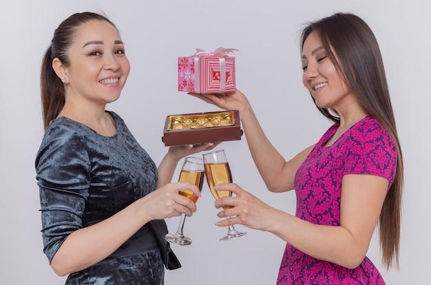 Две счастливые азиатские женщины держат бокалы шампанского и шоколадных конфет