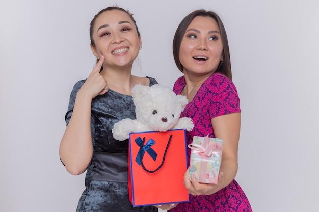 Due donne asiatiche felici che tengono il sacchetto di carta con l'orsacchiotto e il presente che celebra la giornata internazionale della donna che sorride allegramente in piedi sopra la parete bianca