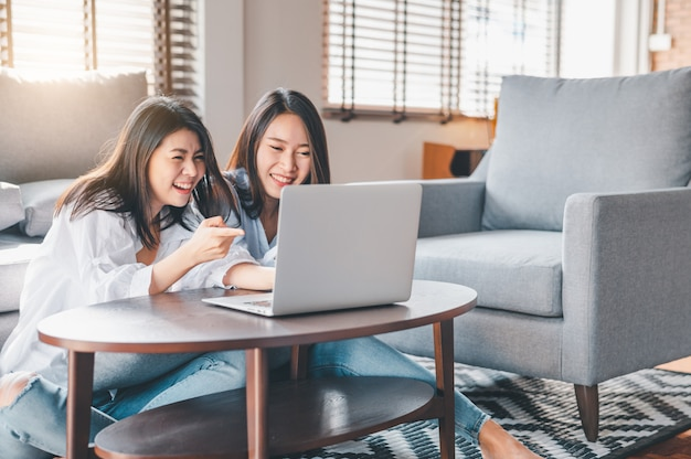 Two happy asian women laughing while working with laptop at home