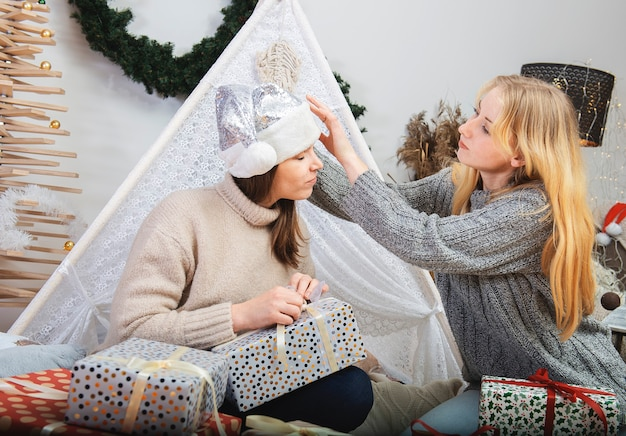 Two happy attractive young women sitting on the floor at home gift wrapping presents for christmas