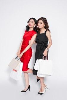 흰색 바탕에 쇼핑백을 든 두 명의 행복한 매력적인 젊은 여성