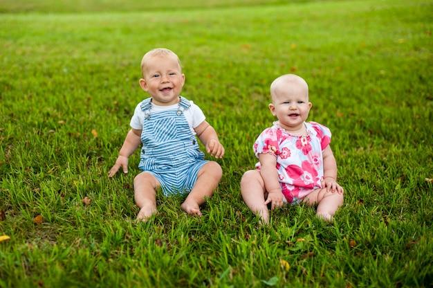 두 행복한 아기 소년과 9 개월 된 소녀, 잔디에 앉아 상호 작용, 이야기, 서로 봐.