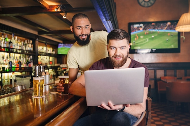 Two happy bearded young men drinking beer and using lapop in pub together