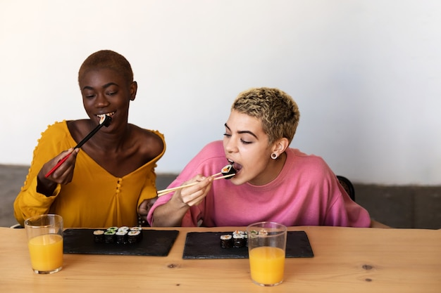 Две счастливые красивые женские пары едят веганские суши-роллы, сидя дома