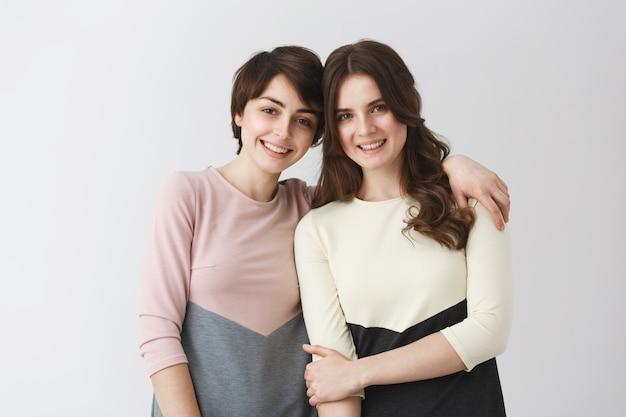 子供の頃から友達になっている2人の幸せな美しい女の子は、勉強のために別の都市に移動する前に家族の写真アルバムにポーズをとっています。