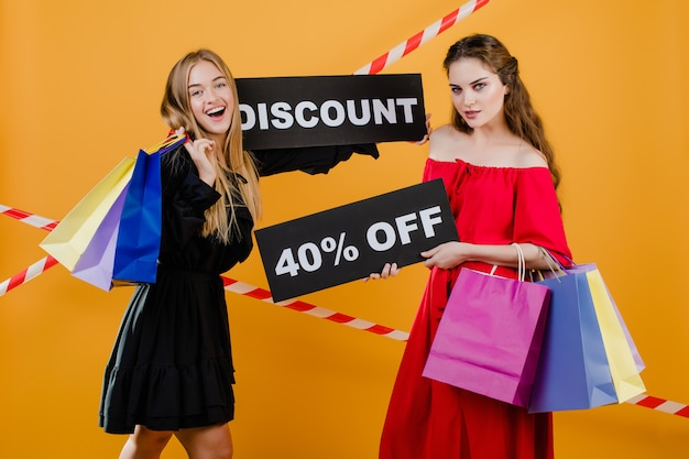 Two happy beautiful girls have discount 40% off sign with colorful shopping bags and signal tape isolated over yellow