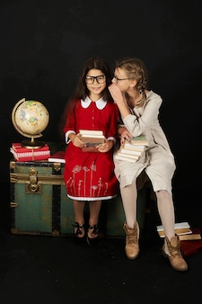 Two happy beautiful schoolgirls with globe and books sitting on chest on a black backgroud