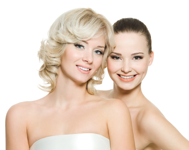 Две счастливые красивые женщины позируют вместе, изолированные на белом