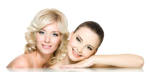 Две счастливые красивые женщины позируют вместе - изолированные на белом