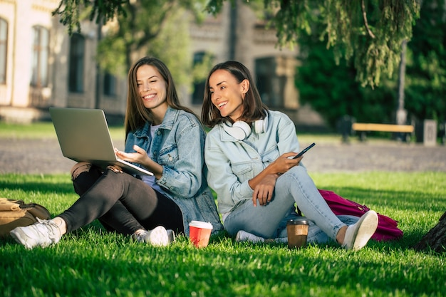 Две счастливые красивые молодые девушки-студентки в повседневной джинсовой одежде отдыхают в парке колледжа с ноутбуком и смартфоном возле университета и пьют кофе.