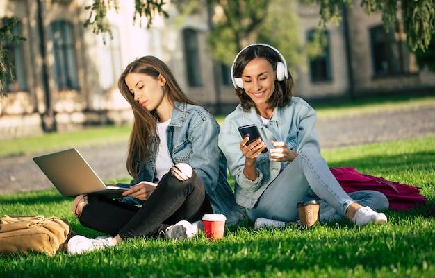 カジュアルなデニムの服を着た2人の幸せな美しい若い学生のガールフレンドは、大学でラップトップとスマートフォンを持って大学の公園でリラックスし、コーヒーを飲みます。