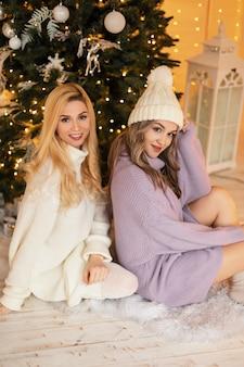 冬休みのクリスマスツリーの近くに帽子と靴下とファッショナブルなニットの服を着て笑顔で2人の幸せな美しい若い女性の姉妹が座っています