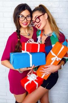 Due migliori amici felici che tengono regali e regali luminosi
