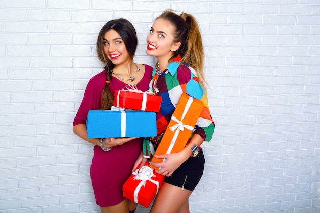 Two happy best friends holding bright gifts and presents