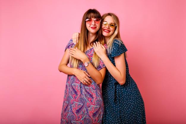 Due felici migliori amiche sorelle donne ragazze che indossano abiti vintage luminosi e occhiali da sole stampati primavera estate alla moda
