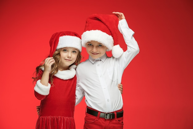Two happy boy and girl in santa claus hats with gift boxes at red studio