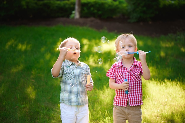 Two happy boy play in bubbles outdoors.