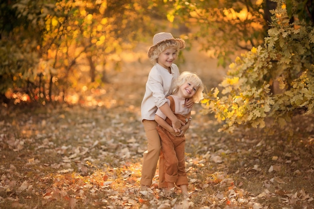 Two happy boys are playing in the park in early autumn