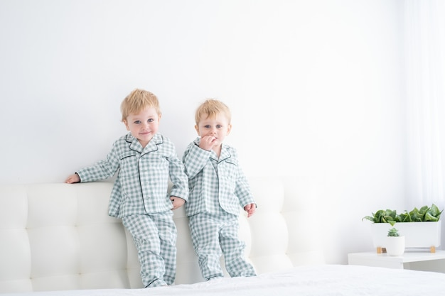 Two happy boys brothers on white bed in pajamas having fun together
