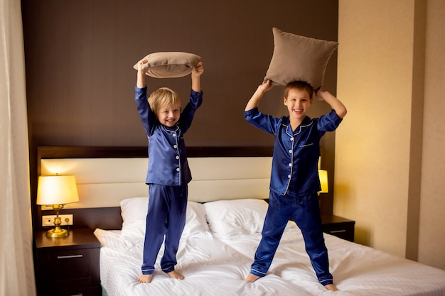 Two happy brother boys jumping on the bed in their pajamas and fighting pillows