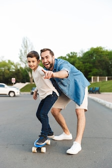 Two happy brothers spending fun time at the park, teaching how to ride a skateboard, pointing away
