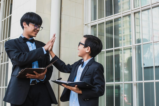Two happy brothers with vintage suit giving high five while holding notebook