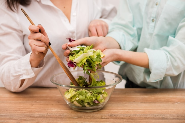 Two happy brunette girls cooking fresh salad together, close-up
