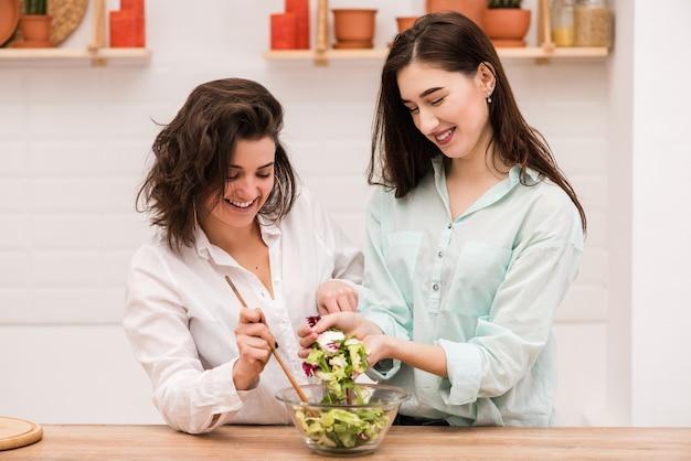Two happy brunette girls cooking fresh salad together