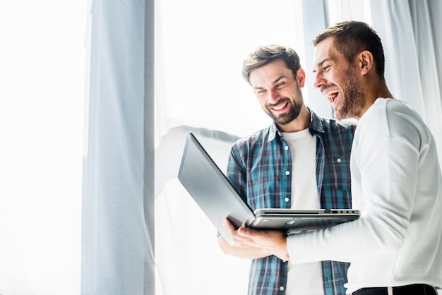 Two happy businessman working on laptop