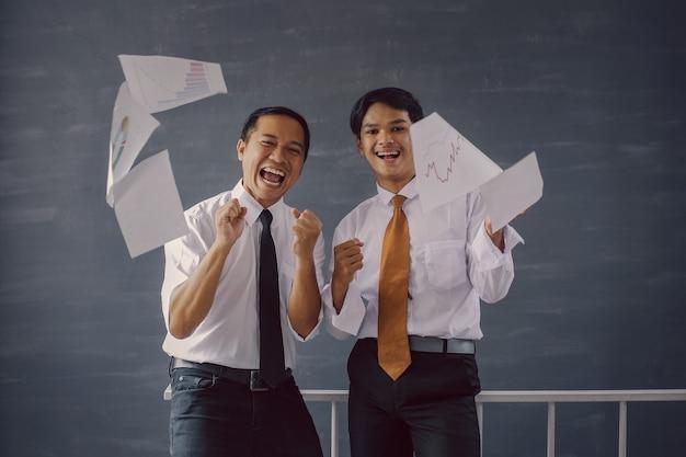 紙のシートが飛び交うことで彼らの成功と成果を祝う2人の幸せなビジネスマン