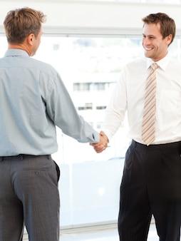 Два счастливых бизнесмена, заключая сделку, пожимая им руки