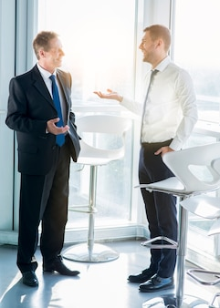 Two happy businessmen standing near window talking with each other in office
