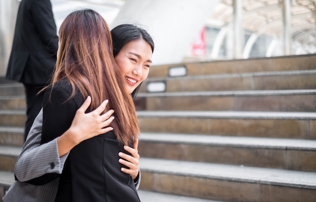 Two happy businesswomen hugging each other outside office building.