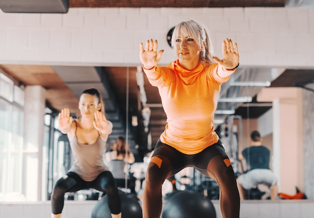 Two happy caucasian women in sportswear doing endurance in squatting position in gym. in background mirror.