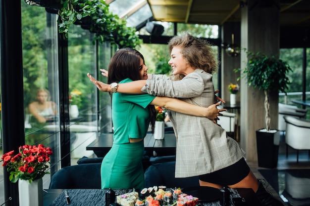 シーフードレストランでランチを楽しんでいる2人の幸せな陽気なガールフレンドまたはビジネスパートナー