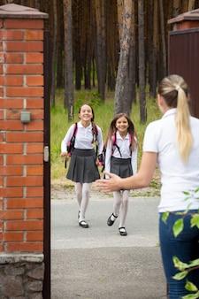 放課後、母親に向かって走っている2人の幸せな陽気な女の子