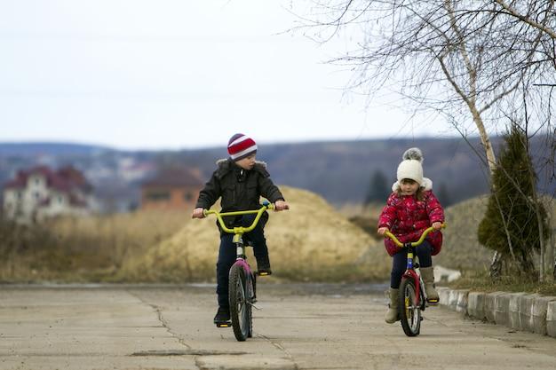 2つの幸せな子供の男の子と女の子の屋外で寒さで自転車に乗る