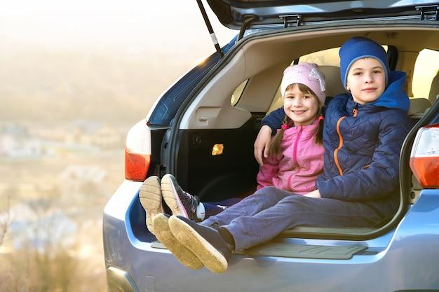 Двое счастливых детей, мальчик и девочка, сидят вместе в багажнике автомобиля