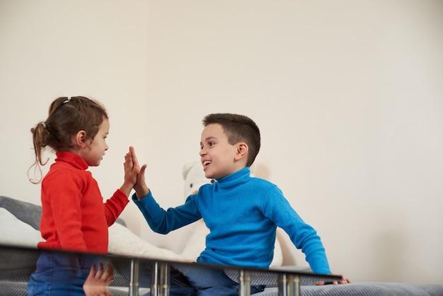 행복한 두 아이가 손뼉을 친다. 어린 시절을 즐기는 형제와 자매