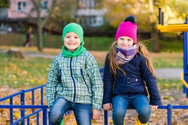 屋外で笑顔の秋の服を着た2人の幸せな子供たち。男の子と女の子が笑顔でカメラを見てください。