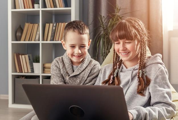Двое счастливых детей, сестра и брат, сидят дома за ноутбуком во время эпидемии вируса